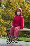 Miúdo que senta-se no banco ao ar livre Foto de Stock Royalty Free