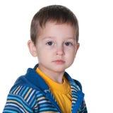 Miúdo sério em um revestimento azul e amarelo listrado fotos de stock royalty free