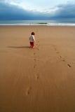 Miúdo solitário na praia Foto de Stock Royalty Free