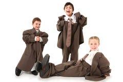 Miúdos adoráveis em ternos desproporcionados fotos de stock