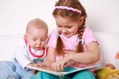 Miúdos adoráveis que lêem e que jogam Imagens de Stock Royalty Free