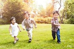 Miúdos asiáticos que funcionam no parque Imagens de Stock Royalty Free