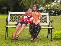 Miúdos asiáticos que jogam na chuva Imagens de Stock