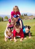 Miúdos bonitos que constroem uma pirâmide humana Imagem de Stock Royalty Free