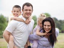 Miúdos carreg de sorriso dos pares em sua parte traseira foto de stock