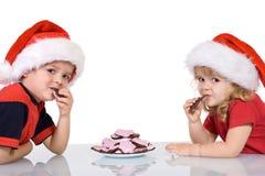 Miúdos com chapéus de Santa que comem bolinhos foto de stock royalty free