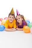 Miúdos com chapéus e balões do partido foto de stock