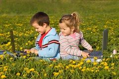 Miúdos com os portáteis no campo de flor fotografia de stock