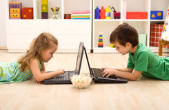 Miúdos com portáteis e uma bacia de pipoca fotografia de stock
