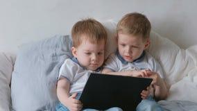 Miúdos com tabuleta Duas crianças dos gêmeos dos meninos que olham desenhos animados na tabuleta que encontra-se na cama video estoque