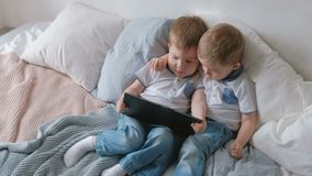 Miúdos com tabuleta Duas crianças dos gêmeos dos meninos que olham desenhos animados na tabuleta que encontra-se na cama vídeos de arquivo