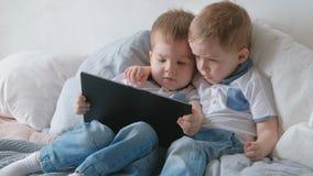 Miúdos com tabuleta Duas crianças dos gêmeos dos meninos que olham desenhos animados na tabuleta que encontra-se na cama filme