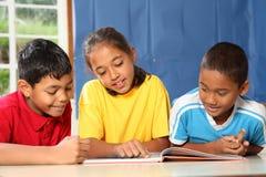 Miúdos da escola preliminar que aprendem junto na sala de aula fotos de stock
