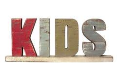 Miúdos da palavra soletrados em letras de madeira Fotos de Stock