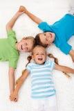 Miúdos de riso felizes no assoalho fotos de stock