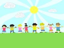 Miúdos em conjunto na grama Fotos de Stock