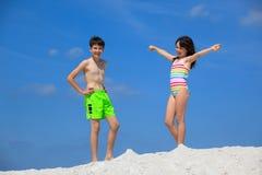 Miúdos em ternos de banho na praia Fotografia de Stock