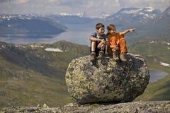 Miúdos em uma pedra grande Foto de Stock Royalty Free