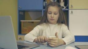 Miúdos espertos A estudante pequena está sentando-se na mesa e está usando-se o portátil video estoque