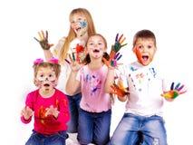 Miúdos felizes com as mãos pintadas em pinturas coloridas Imagens de Stock