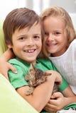 Miúdos felizes com seu animal de estimação novo - um gatinho pequeno Foto de Stock Royalty Free