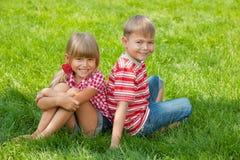 Miúdos felizes na grama Fotos de Stock