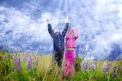 Miúdos felizes no prado do lupine Imagem de Stock