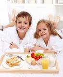 Miúdos felizes que comem o pequeno almoço na cama Fotografia de Stock