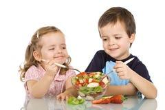 Miúdos felizes que comem a salada de fruta imagens de stock