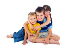 Miúdos felizes que compartilham de um hug Imagem de Stock Royalty Free