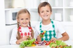 Miúdos felizes que preparam uma refeição na cozinha Fotos de Stock