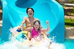 Miúdos na corrediça de água   Fotografia de Stock