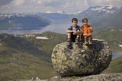 Miúdos na pedra grande nas montanhas Fotos de Stock
