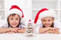 Miúdos no tempo do Natal com árvore do pão-de-espécie Imagem de Stock