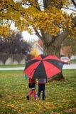 Miúdos que andam com guarda-chuva foto de stock