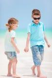 Miúdos que andam na praia fotografia de stock