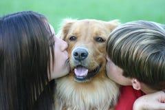 Miúdos que beijam o cão Fotografia de Stock Royalty Free