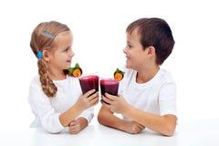 Miúdos que clinking com suco fresco imagens de stock