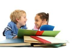 Miúdos que coloc e que lêem um livro Foto de Stock Royalty Free
