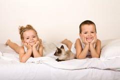 Miúdos que colocam na cama com seu gatinho fotos de stock royalty free