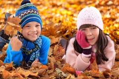 Miúdos que colocam nas folhas de outono Fotos de Stock Royalty Free