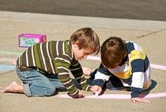 Miúdos que colorem com giz imagens de stock