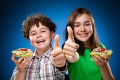 Miúdos que comem sanduíches saudáveis fotografia de stock