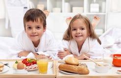 Miúdos que comem um pequeno almoço saudável na cama Foto de Stock Royalty Free