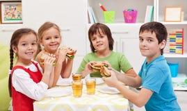 Miúdos que comem um petisco em sua sala fotos de stock