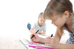Miúdos que desenham e que lêem Fotografia de Stock Royalty Free