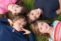 Miúdos que encontram-se na grama Fotos de Stock