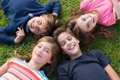 Miúdos que encontram-se na grama Foto de Stock Royalty Free