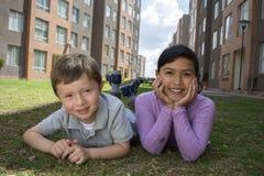 Miúdos que encontram-se na grama Fotografia de Stock Royalty Free