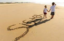 Miúdos que escrevem na areia foto de stock royalty free